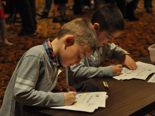 Twins Braden (left) and Brandon Delacerda write letters to Santa Claus on Sunday before his arrival to the Country Inn & Suites in Pineville.
