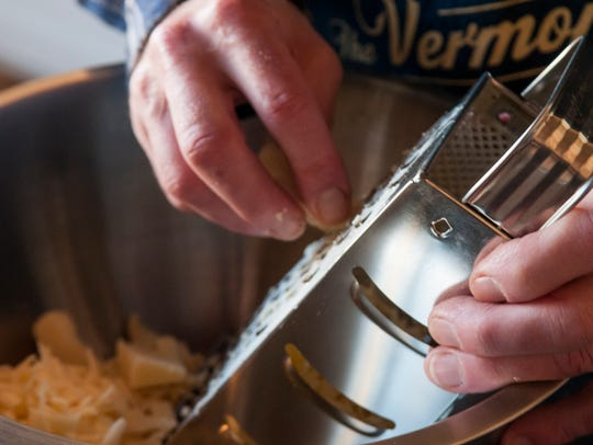 Cabot Orton grates cheese while cooking recipes from