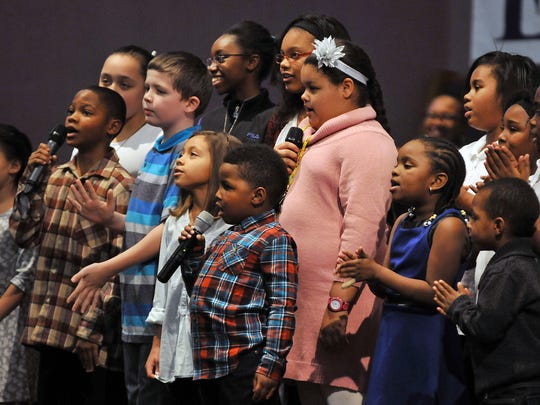Members of the Community Choir sing during the Martin Luther King, Jr. Commemoration Service at the Oasis of Love Church Sunday evening.