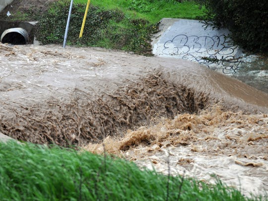 Runoff from Tuesday's storms rushes down Santa Rita Creek by Russell Road in Salinas.
