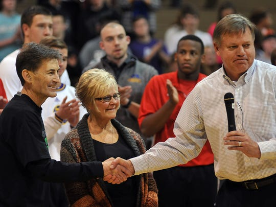 Ontario coach Joe Balogh shakes hands with John Gurney as his wife looks on during ceremonies prior to a benefit basketball game on his behalf between Mansfield Christian and host Lexington in November.