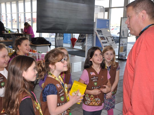 Members of Brownie Troop 80067 talk to Mark Stader, who came in to Jennings Chevrolet Buick GMC on Saturday and guessed how many Girl Scout cookies were packed in the trunk of a Chevrolet Cruze.