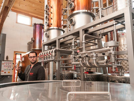 Chris Maggiolo, production manager and distiller, stands next to the still at Silo Distillery in Windsor, Vt.