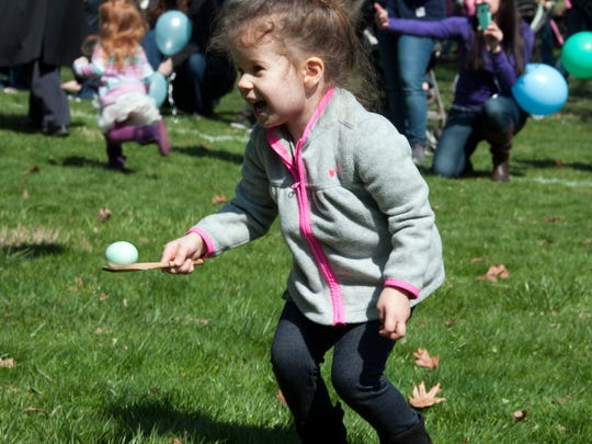 Theia Tucker, 3, of Fremont, smiles while carrying an egg in last year's Easter Egg Roll at the Rutherford B. Hayes Home and Museums. This year's Easter Egg Roll starts at 2 p.m. Saturday.