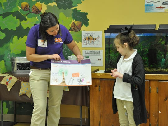 Kylie Bush (right) presents her design for the T.R.E.E. House Children's Museum's new playground to Courtny Dolan, project manager with KaBOOM!, and other museum members.