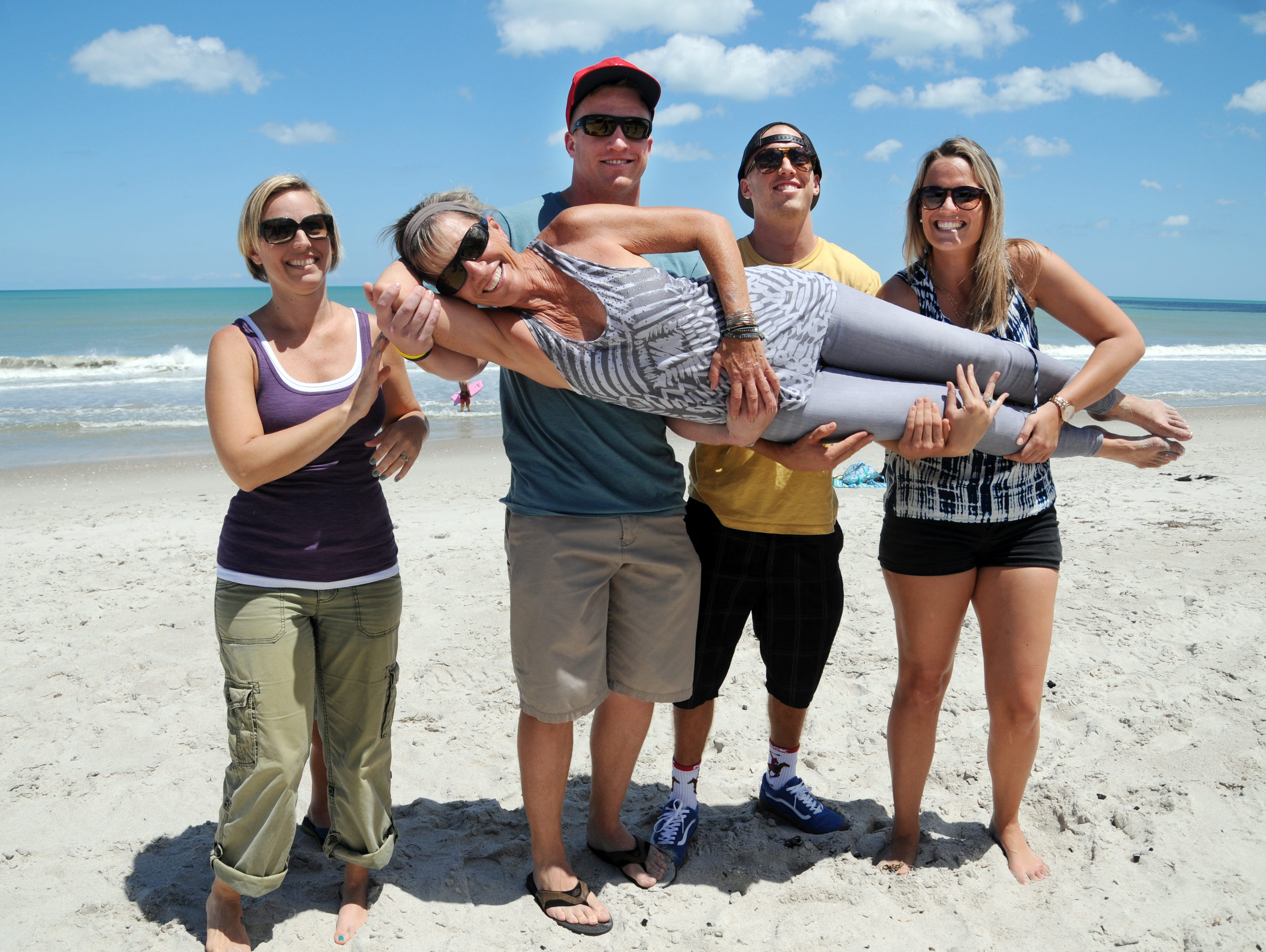 Linda Anderson gets held up by her children Tiffany Brown, and Mason, Calvin and Madison Smith on the beach in Satellite Beach Saturday afternoon.