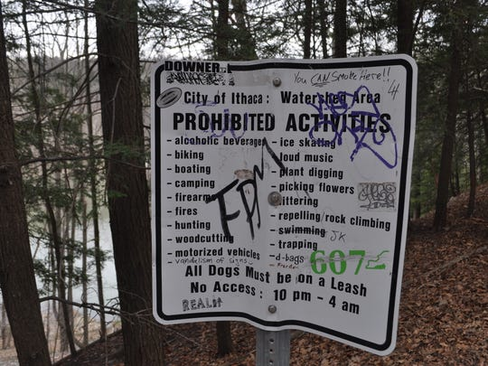 A defaced sign on a trail leading to Second Dam on Six Mile Creek.