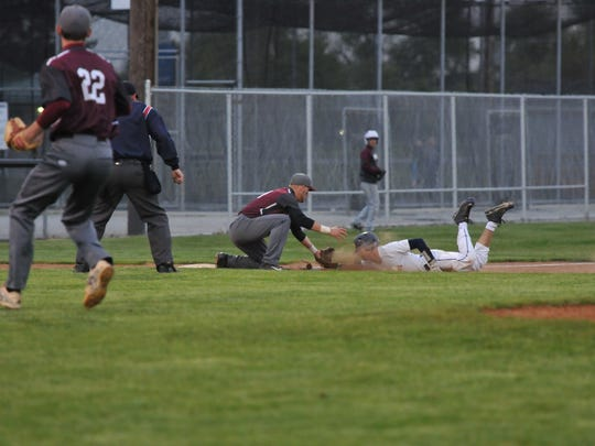 Woodmore's Matt Depner is safe at third Monday as Genoa's Matt Bradfield knocks down the throw.