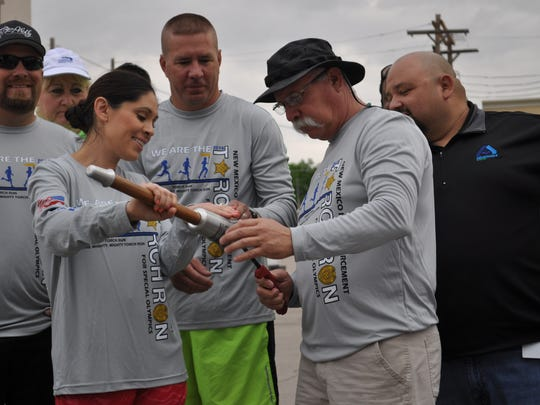 Carlsbad Police Department Office Anna Austin attempts to light the Special Olympic Torch.