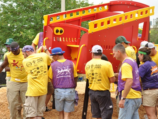 Volunteers install playground equipment, including