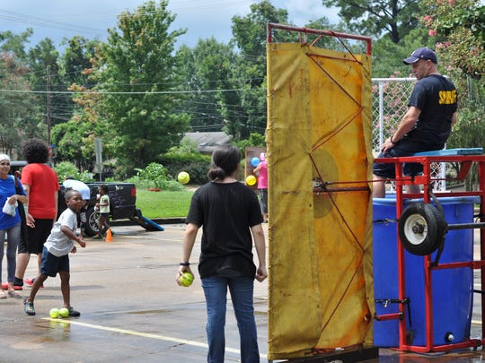 Rapides Parish Sheriff's Office deputies take turn in a dunking booth at an event Wednesday to celebrate the end of summer with free books and activities for kids.