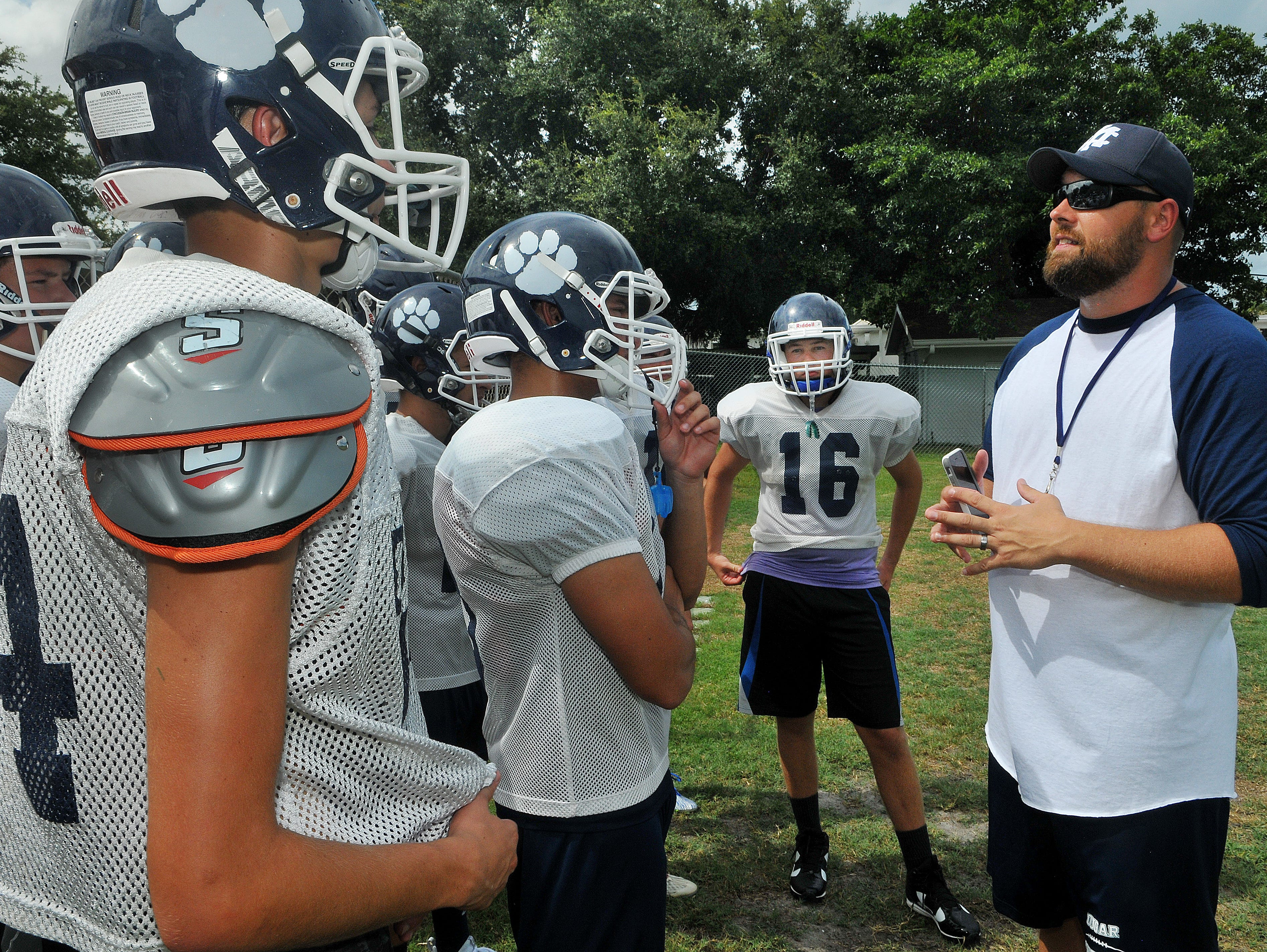 Merritt Island Christian Head Football coach Jamie Bopp talks with his players during Wednesday's practice held at the Deen Athletic Training Facility on Merritt Island.