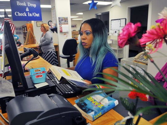 Alake Davis of Titusville, a circulation supervisor, works the front desk of the Mims/Scottsmoor Public Library.