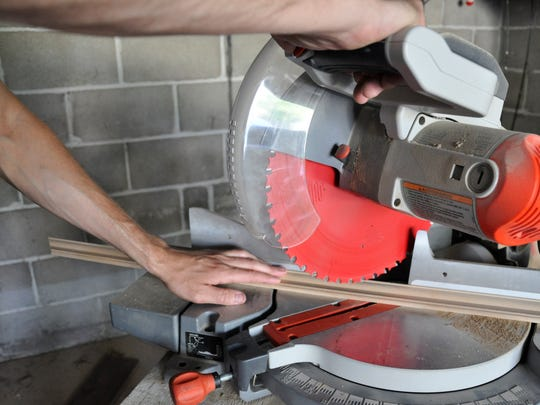A chop saw is used to cut the framing material at a 45-degree angle.