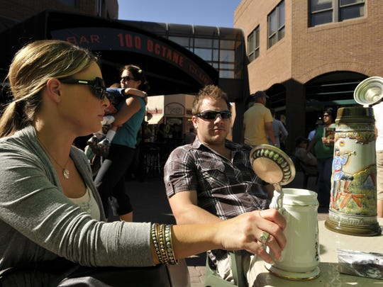 Holly Fischer and Mike Weaver sit with their beer steins at a 2010 Oktoberfest celebration in Fort Collins