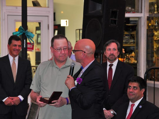 Rick St. Pierre, center, holding the microphone, received the Spirit of Somerset John Graf Memorial Award. He is shown talking with Robert Graf as Somerset County freeholders, from left, Mark Caliguire, Brian D. Levine and Patrick Scaglione look on.