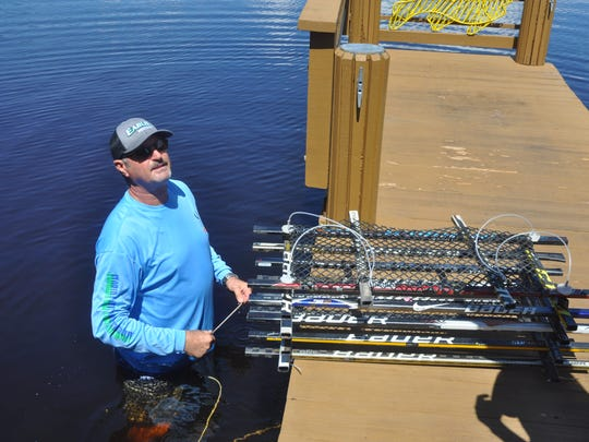 Bob Wasno puts the new structure made from hockey sticks under a dock at Coconut Jacks in Bonita Springs.