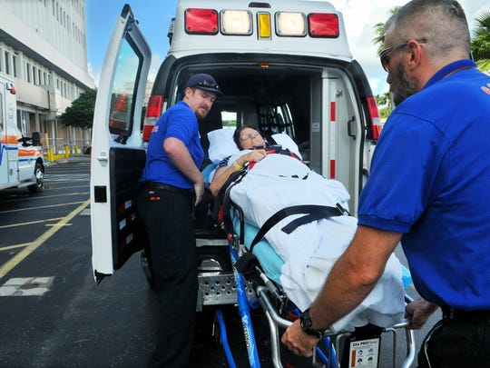 Keith Nelson and Jason Greene, with Coastal Health Systems ambulance service, evacuate patient Linda LaPorta of Cocoa Beach from Cape Canaveral Hospital on Wednesday. In preparation for the impact of Hurricane Matthew, the hospital evacuated 64 patients using 22 ambulances.