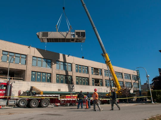 The new air conditioning unit is hoisted onto the roof Monday, Oct. 10, outside the Sperry's MovieHouse in Port Huron.