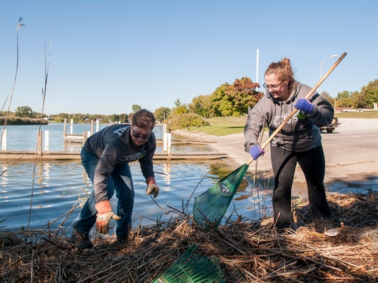 Charlene MacRae, left, and Tabitha Systermann clean up the river front Monday, Oct. 10, at the Riverside Boat Launch in Port Huron.