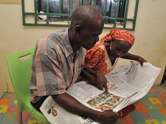 Abana Muta, left, and Hawa Abana, right, look at photos of the freed twenty-one Chibok schoolgirls in newspaper including their daughter Blessing Abana, in Nasarawa Nigeria, Saturday, Oct. 15, 2016. Conflicting reports emerged Friday about whether the first negotiated release of some Chibok schoolgirls kidnapped by Boko Haram in Nigeria in 2014 involved a ransom payment, a prisoner swap for Islamic extremist commanders, or both.