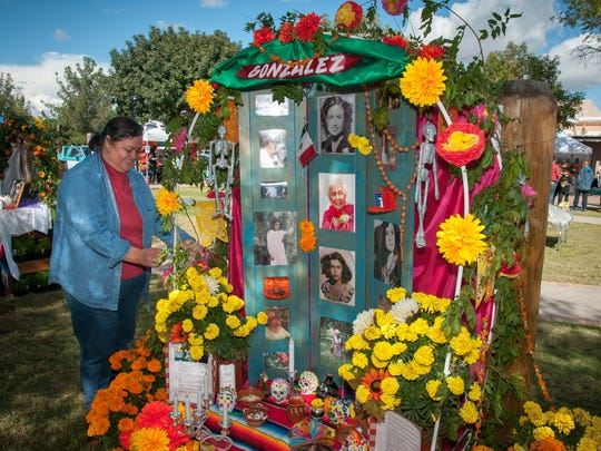 Lupe Garcia adds flowers to the shrine to her mother, Maria Gonzalez, on Mesilla Plaza, last year. It took Garcia and over a dozen other family members two hours to build the shrine.