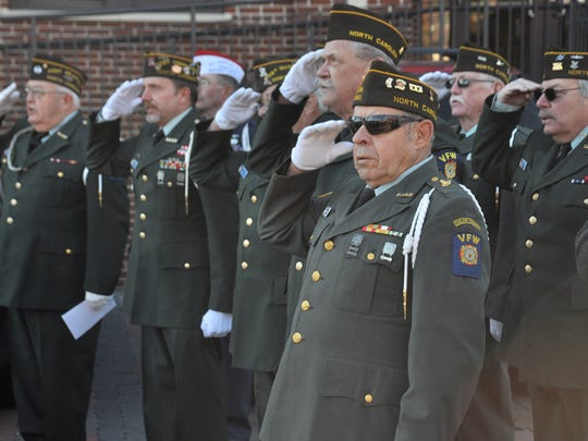 Veterans in the Mars Hill V.F.W. Post 5483 salute during the singing of the national anthem.