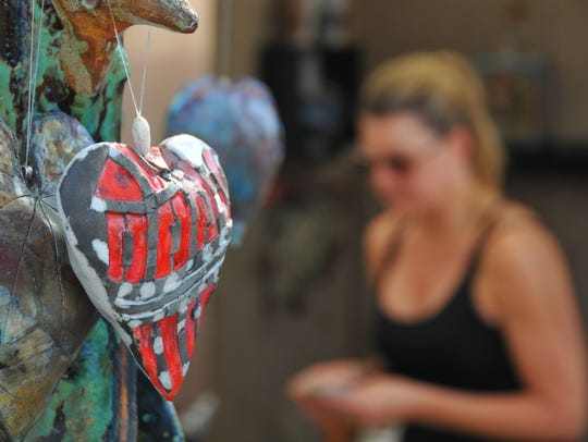 Christi Damm  admires the art of artist Lynn Merhige,