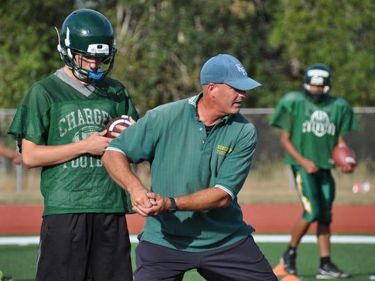 Kentridge High coach Marty Osborn, a Bremerton native, shows his quarterbacks the proper way to fake a handoff prior to the 2015 season. Osborn recently resigned after a winless season.