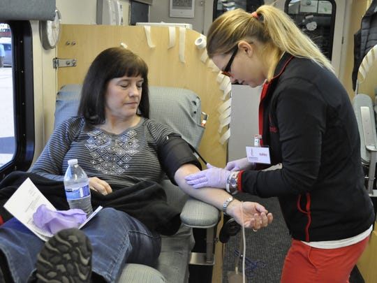 Rhonda Hanlon, of Sioux Falls, donates blood in the Heroes Behind the Badges blood drive Dec. 27, 2016. Hanlon and her family went to Camille's Cafe to donate blood in honor of Sioux Falls police. The drive puts Sioux Falls police and fire departments in competition to see who can bring in the most blood donations in their name.