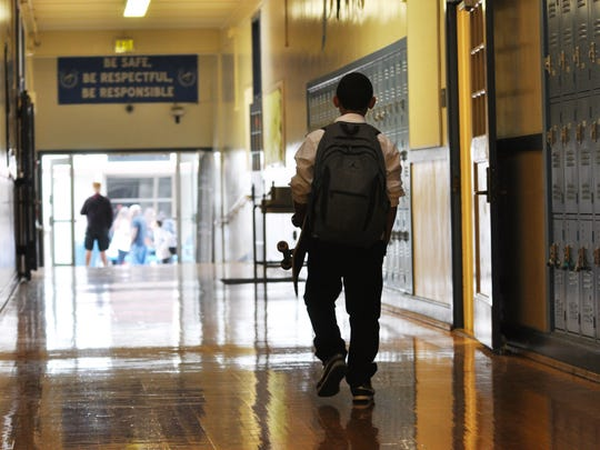 A youngster with a skateboard makes his way down a long hall on Wednesday, August 3rd, the first day back to school for over 1200 students and staff at Washington Middle School, part of the Salinas Union High School District in Salinas, CA.