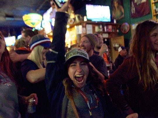 Fans celebrate Sunday at the Trailhead Tavern in Fort Collins during the Super Bowl. The Broncos won 24 to 10 over the Carolina Panthers.