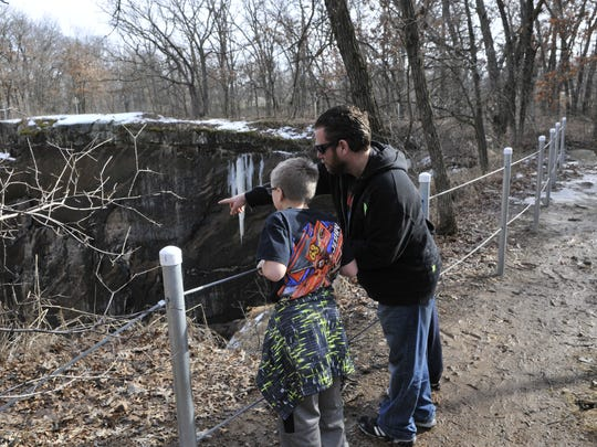 Brian Jambor and his son Lewis stop and look at a quarry while hiking on Sunday at Quarry Park.