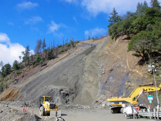 A bulldozer moves earth Thursday at the site of a rock slide on Highway 299 about 30 miles west of Weaverville.