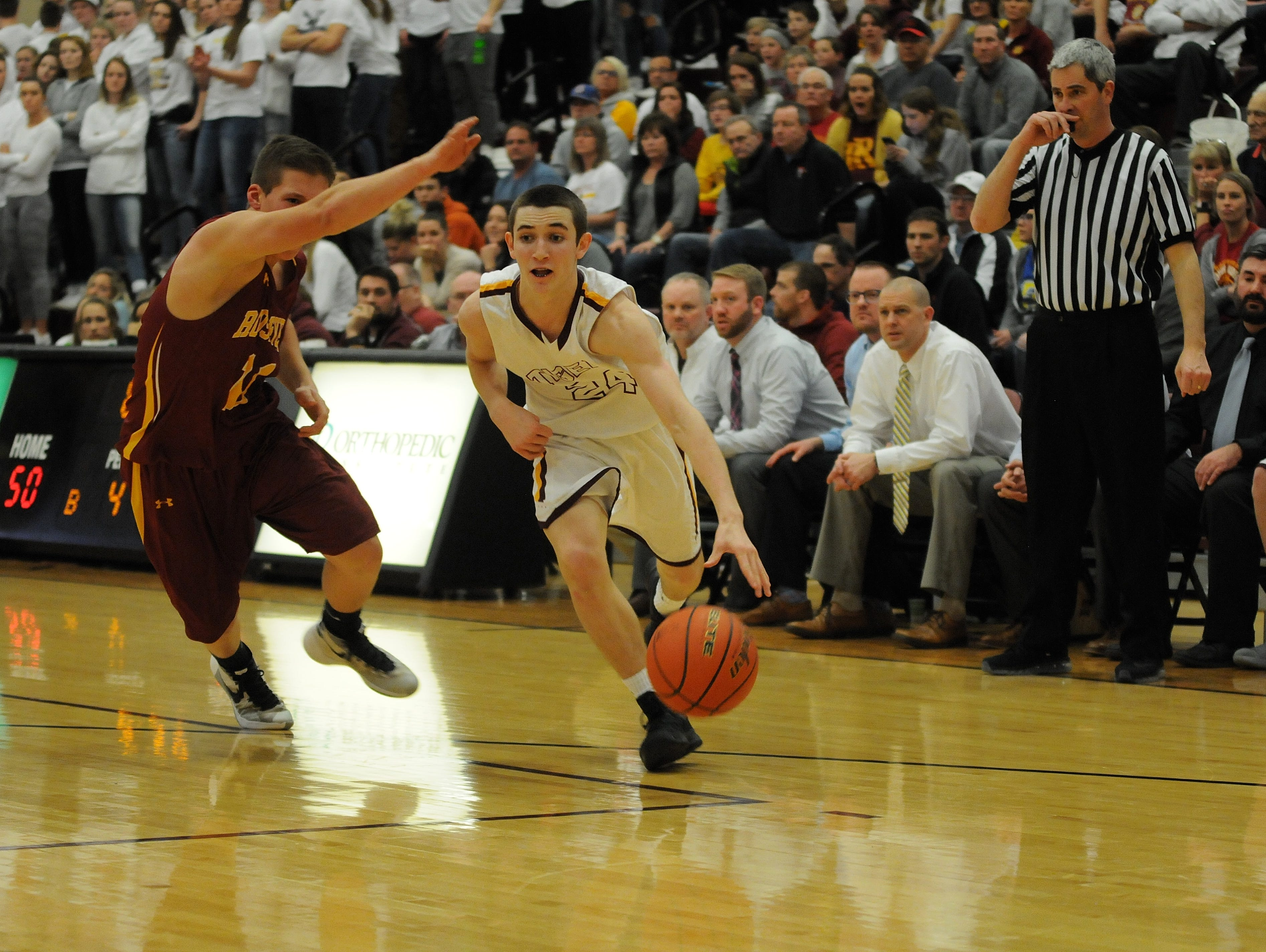 Harrisburg's Nick Hoyt drives around SF Roosevelt's Austin Portner during the Region 1AA game in Harrisburg on Tuesday night. The Tigers won 71-52 to earn their first trip to state in Class AA and first since 2001.