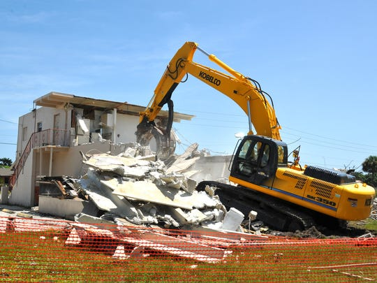 An excavator demolishes the dilapidated Evans Grocery