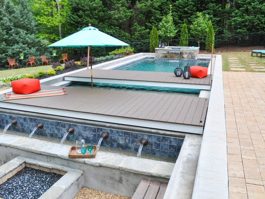 This undated photo provided by Chip Wade and Wade Works shows a pool area with movable platforms, and concealable hot tub, which make for a multi-use backyard in Johns Creek, Ga., that cleverly maximizes the square footage.