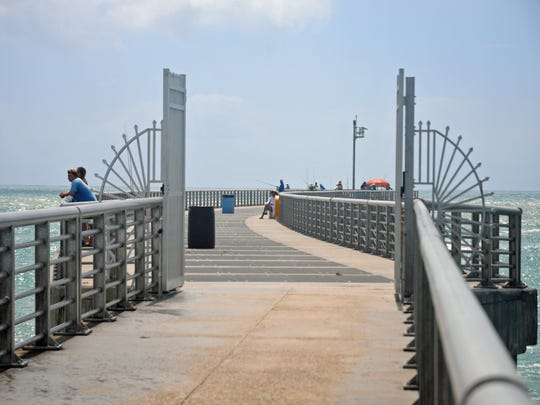 Iron gates are open, allowing access to the end of the Sebastian Inlet pier. The end of the pier recently reopened after damage from Hurricane Matthew was repaired.