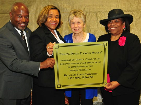 Left to right, Lt. Col. Michael Hales, director of the DSU Aviation Program; College of Business Dean Donna Covington; JoAnn Coons, widow of Dr. Coons; Dr. Wilma Mishoe, DSU Board of Trustees member, hold a copy of the plaque that is being created for the Daniel E. Coons Hangar.