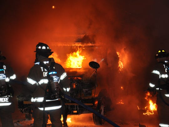 Firefighters battle a school bus fire in the early morning hours of May 26.