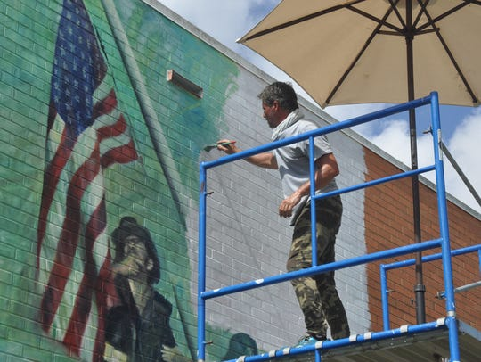 Laurent Dareau paints a mural on the side of the Bonita