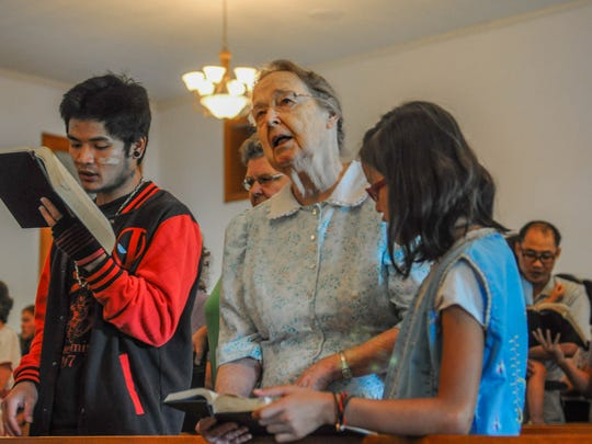 Miriam Charles worships beside Paday Shee, left, and Paw Shee. Paday, 25, and Paw, 10, are not related but are both part of the group of ethnic Karen refugees who attend Habecker Mennonite Church in Lancaster County, Pennsylvania.