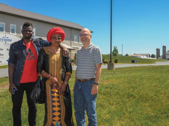 Congolese refugee Rachel Bunkete (center), her son Shadrack and Keith Rohrer, pastor at Keystone Church in Paradise, Pennsylvania, stand outside Keystone Church. The church has offered help to the Bunkete family since 2013.