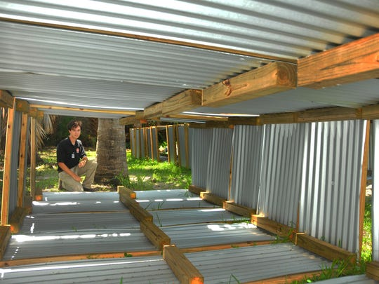 Zach Eichholz looks through some of the 4-by-8-foot plant beds made of wood and steel that will be part of Satellite Beach's community garden.