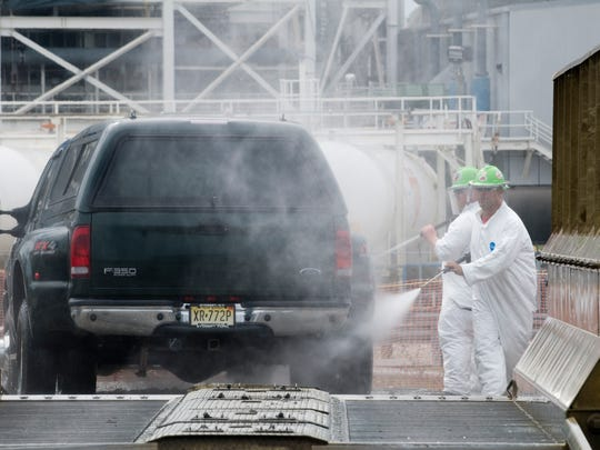 Workers spray down a vehicle leaving the cleanup area of the Kingston Fossil Plant coal ash spill site on Wednesday, September 23, 2009. All vehicles leaving the site must be cleaned as part of the cleanup, which could cost as much as $1.2 billion.