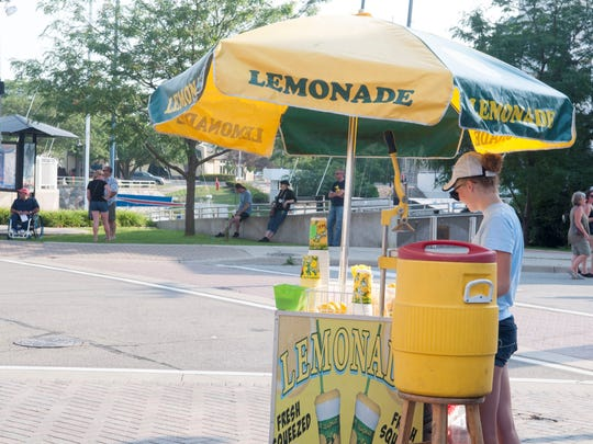 A lemonade stand sits at the corner of Huron and Quay during Boat Night.