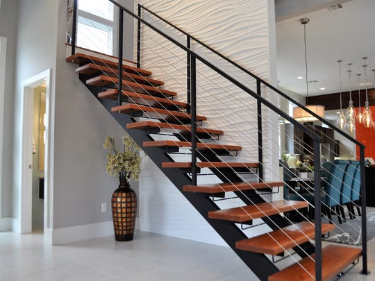 The entrance features a beautiful staircase and soaring ceilings.