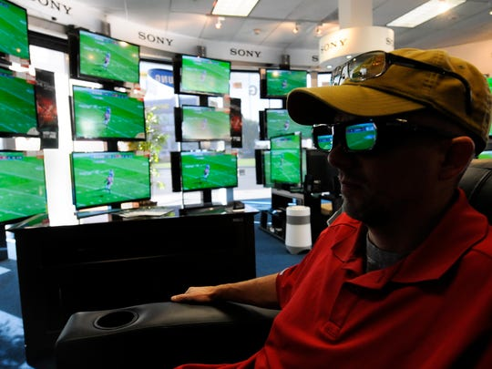 Shopper Brad Pauley looks over 3DTVs at a Video & Audio