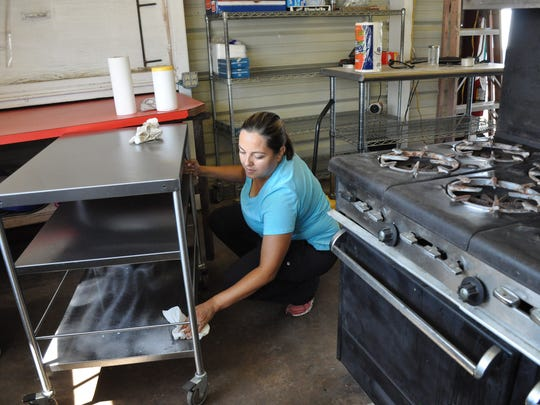 Karina Escobedo and several others clean the Mi Ranchito food booth at Taylor County Expo Center before the 2017 West Texas Fair & Rodeo. Local businesses have joined nonprofits to occupy booths at the annual fair.