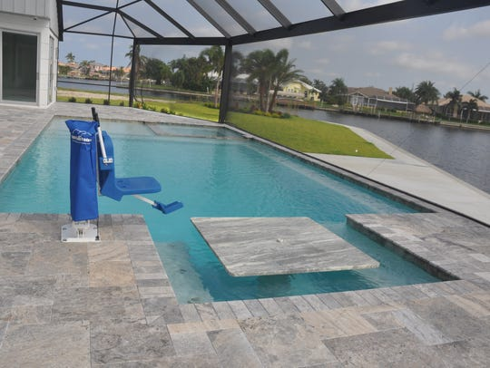 The pool has a table, bench area and a lift to help